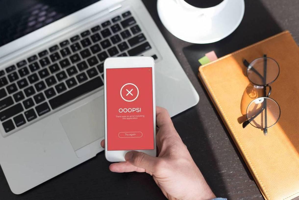 Hand holding smartphone showing app install error screen