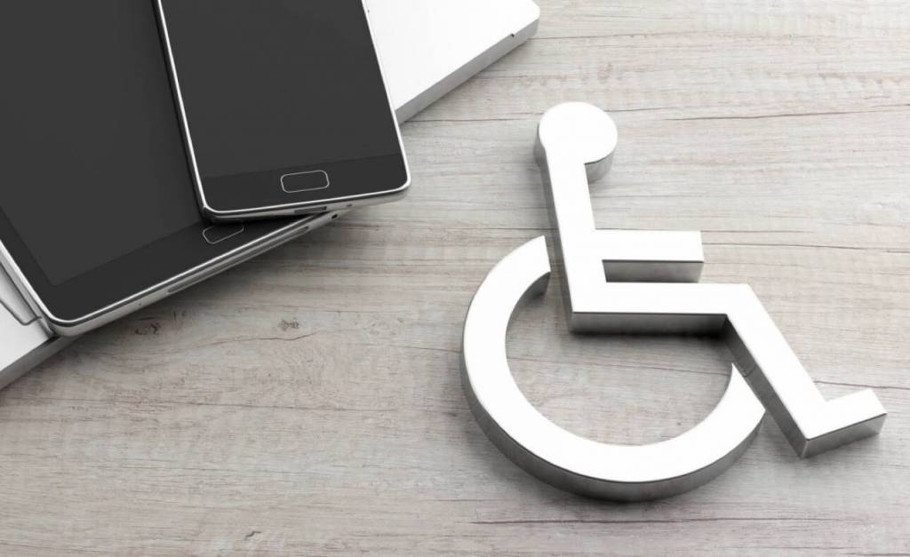 Laptop and mobile devices with wheelchair icon on wooded surface