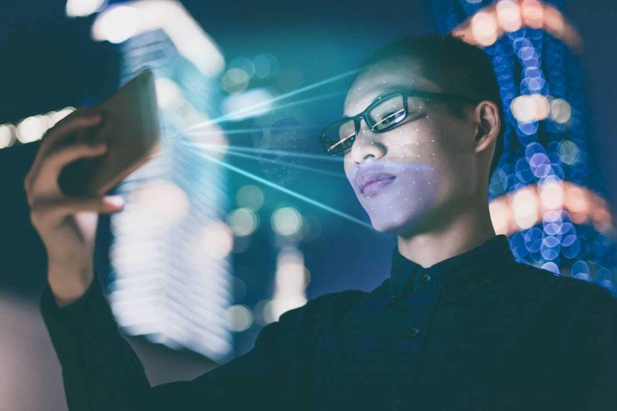 Businessman using smartphone face recognition outdoors at night