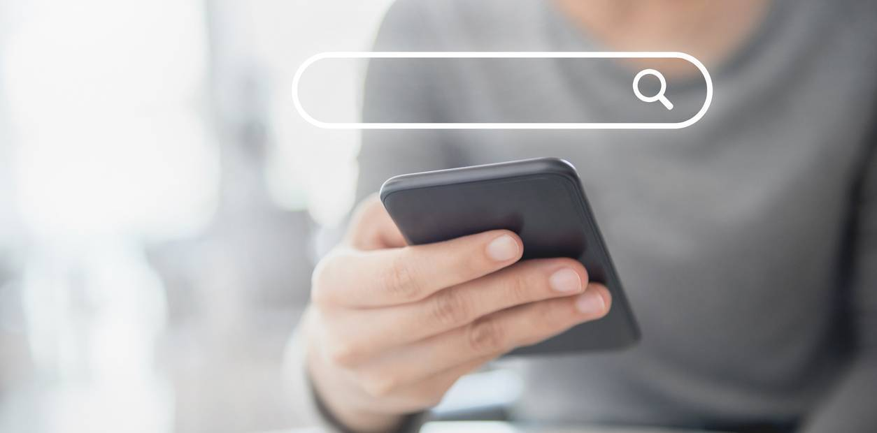 person holding smartphone and searching online